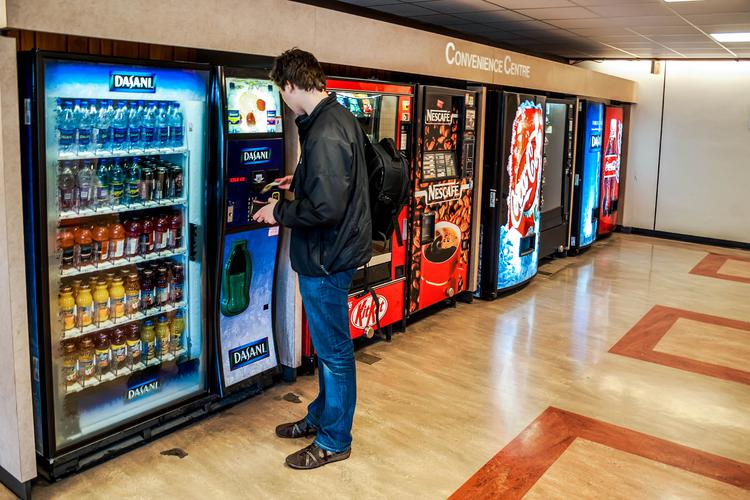 Man ordering a beverage from a vending machine